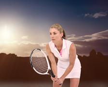 Athlete playing tennis with a racket  against composite image of landscape Stock Photos