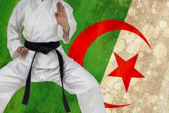 Fighter performing karate stance against algeria flag in grunge effect - stock photo