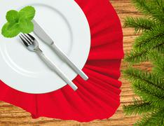 Fork, knife and white plate on a red cloth and christmas tree on wooden table - stock photo