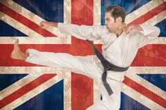 Fighter performing karate stance against union jack flag in grunge effect Stock Photos