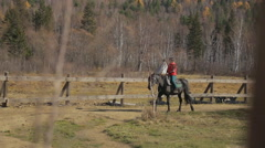 The woman is riding a horse in the circle road of the paddock. The hoofed Stock Footage