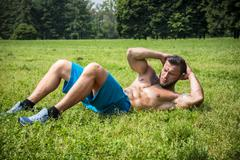 Bearded sportsman doing abs exercise in park - stock photo