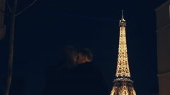 Lovers whiling time at night in Paris at the Eiffel tower - stock footage