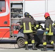 Firemen in action during the road accident Stock Photos