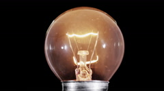 Edison lamp light bulb blinking over black, macro view, looped Stock Footage