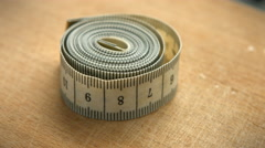 Measuring tape rotating around a wood piece Stock Footage