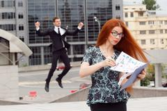 Red-haired woman posing on jumping businessman background Stock Photos