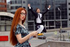 Red-haired woman posing on jumping businessman background - stock photo