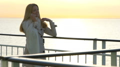 A young woman uses a smartphone to the deck of the liner in the sun. Slow Motion Stock Footage