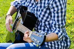 girl on a green meadow playing guitar - stock photo