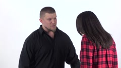 Annoyed man yells at woman and grabs her by shoulders - stock footage