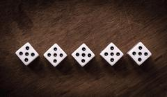 Number five dice on wooden table - stock photo