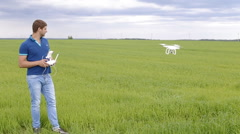 Guy using remote control to film aerial video with drone mounted camera, robot Stock Footage