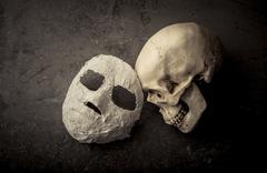 Human skull and white face mask on stone background. - stock photo