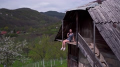 Woman sitting on balcony of a wooden house, mountains Stock Footage
