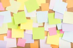 Empty blank sticky notes on notice board in office Stock Photos