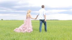 Young couple in love holding hands walking in field at sunset. - stock footage