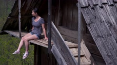Sexy girl on balcony of a wooden house, green valley Stock Footage