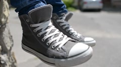 Man moves his feet in sneakers Converse All Stars - stock footage