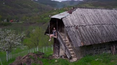 Woman relaxing on balcony of a wooden house, green valley Stock Footage