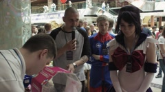 Man with microphone stay at lottery box. Shopping center. Girls in anime suits - stock footage