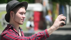 Man Gay makes Photo Selfie via Mobile Cell Phone in a city street - stock footage