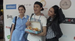 Girls posing with asian boy holding box with doughnuts at stand. Entertainment Stock Footage