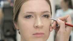 Makeup artist making make-up for young model - stock footage