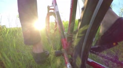 Slow motion cyclist man rides through the tall grass, low wide angle Stock Footage