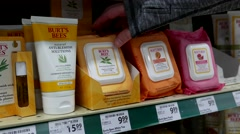 Woman selecting Burt's bees facial cleaning towelette in Save on Foods store Stock Footage