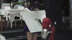 Girls in anime suits draws poster by marker in shopping center. Entertainment - stock footage