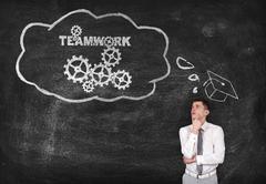 businessman thinks of effective teamwork - stock photo