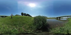 360Vr Video Man Comes Sits Down on a Ground Green Meadow Reed Small River or Stock Footage