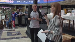 Woman and man with microphone in shopping center. Entertainment event. Hosts - stock footage