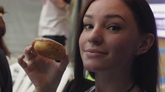 Young girl posing on camera with doughnut covered by glaze at table. Contest Stock Footage