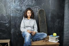 Young cute teenage girl in classroom at blackboard seating on table smiling Stock Photos