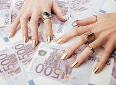 Hands of rich woman with golden manicure and many jewelry rings on cash euros Stock Photos