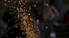 Slow motion shallow focus golden sparks shooting upward man in soft focus in BG Stock Footage