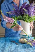 Woman arranging a bunch of flowers in a vase Stock Photos