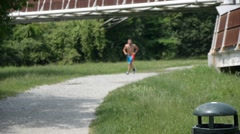 Shirtless muscle man jogging on pathway - stock footage