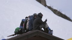 Ski resort. Snowboarders sitting on roof of house in encamp. Crowd of people Stock Footage