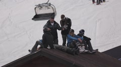 Ski resort. Snowboarders sitting on roof of house in encamp. Ski lifts ride Stock Footage