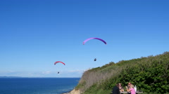 Paragliding from a cliff or directly from the beach below Stock Footage