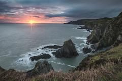Dramatic stormy sunrise landscape over Bull Point in Devon England Stock Photos