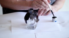 Man painting a glass skull in black - stock footage