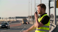 Traffic police with walkie talkie work at highway Stock Footage