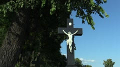 Jesus Christ on the cross at the cemetery under a linden tree - stock footage