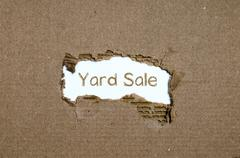 The word yard sale appearing behind torn paper. Stock Photos