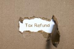 The word tax refund appearing behind torn paper. Stock Photos