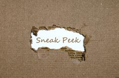 The word sneak peek appearing behind torn paper. Stock Photos